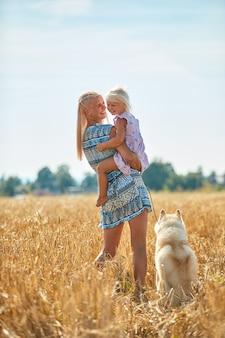 Neonata sveglia con mamma e cane sul campo di grano. la giovane famiglia felice gode del tempo insieme alla natura. mamma, piccola neonata e cane husky che riposano all'aperto. insieme, amore, concetto di felicità.