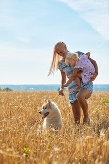 Neonata sveglia con mamma e cane sul campo di grano