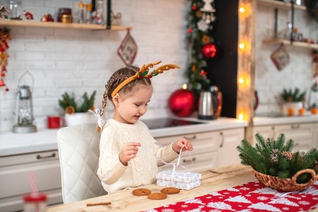 Bambino sveglio in maglione leggero e fascia con corna di renna seduto al tavolo della cucina che sorride apre la confezione regalo