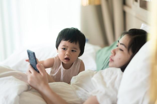Bambino sveglio che osserva il telefono cellulare con la madre e che si siede sul letto