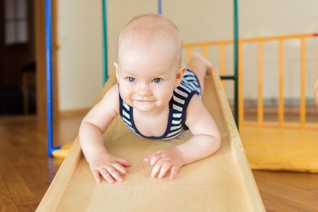 Il bambino sveglio esegue esercizi ginnici su scale e anelli complessi sportivi domestici in legno.