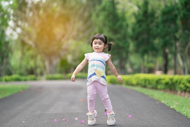 Bambino carino che gioca e salta in giardino, concetto di attività all'aperto per bambini carino