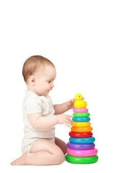 Bambino sveglio che gioca con la piramide variopinta dell'arcobaleno isolata su una priorità bassa bianca. bambino con giocattolo educativo.