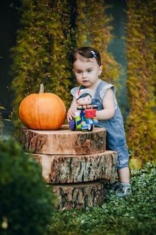 Bambino sveglio che gioca con il suo giocattolo nel loro cortile accanto ai ceppi decorativi con la grande zucca