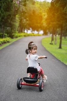 Bambino carino in bicicletta in giardino