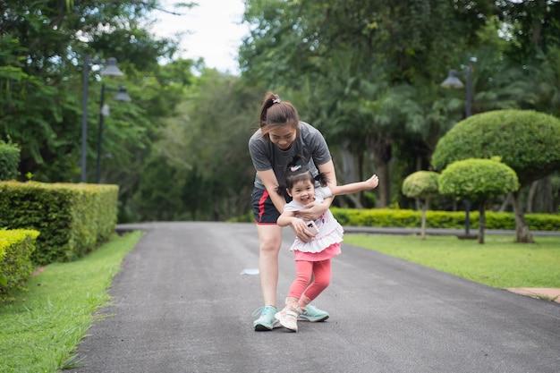 Bambino carino che corre con sua madre in giardino, concetto di famiglia felice