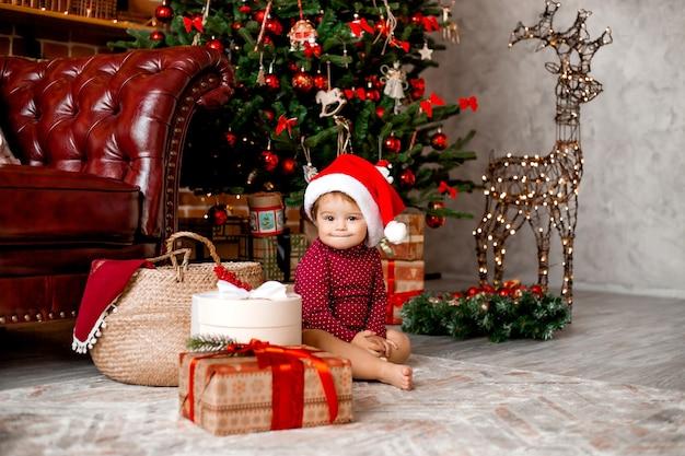 Il bambino sveglio santa si siede a casa vicino all'albero di natale con i regali