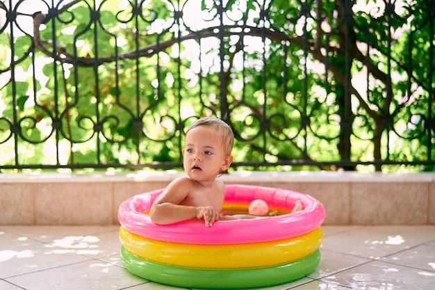 Il bambino carino si siede nella mini piscina gonfiabile tornando indietro