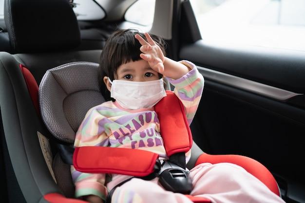 Bambino sveglio che si siede in un seggiolino per auto