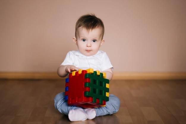 Fare da baby-sitter sveglio sul pavimento della casa che gioca con un cubo multicolore