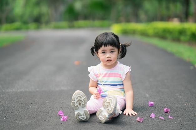 Bambino sveglio che si siede al giardino, concetto di attività all'aperto del bambino sveglio