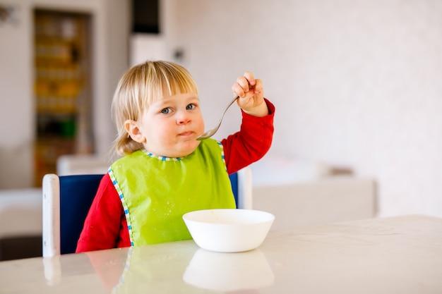 Bambino sveglio che si siede sulla sedia dei bambini alti e mangia verdura da solo nella cucina bianca.