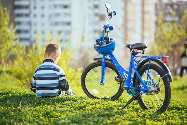 Simpatico bambino seduto vicino alla sua bici al tramonto