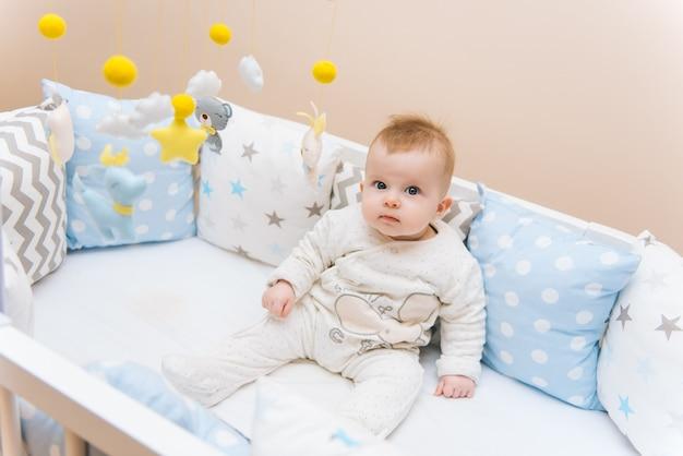 Bambino sveglio che si siede in un letto rotondo bianco