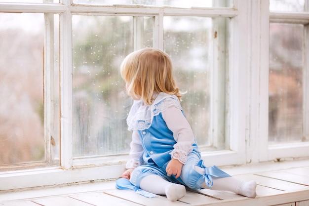 Bambino sveglio che si siede sul davanzale della finestra e guardando fuori dalla finestra
