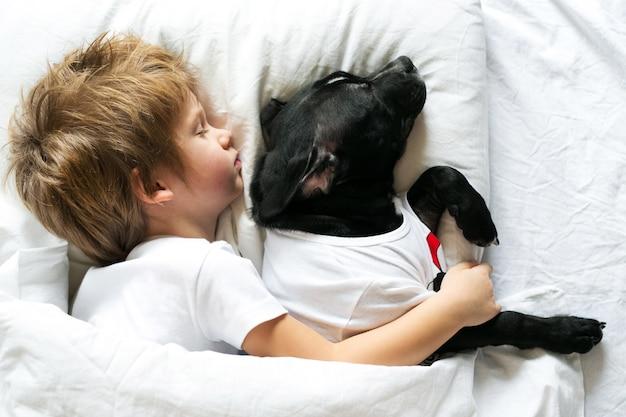 Bambino sveglio che dorme con il suo cane