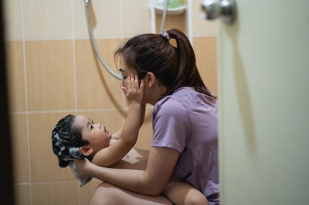 Il bambino carino fa la doccia con sua madre in bagno