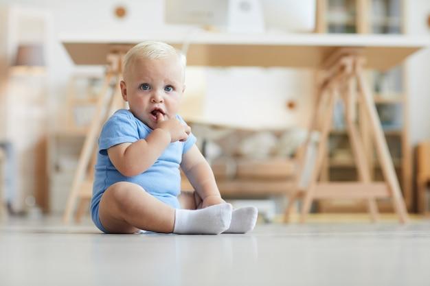 Bambino sveglio con capelli biondi e occhi azzurri che si siede sul pavimento con il dito in bocca