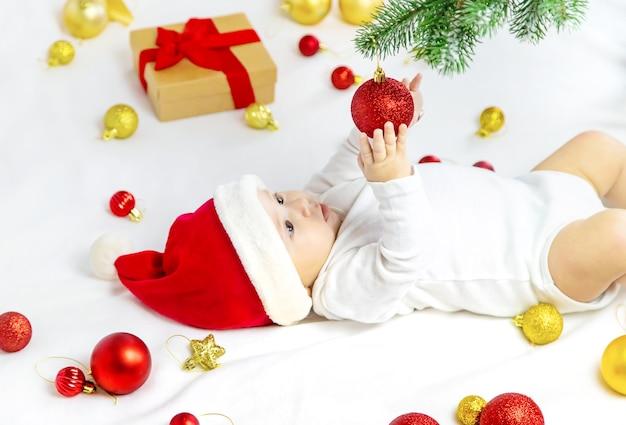 Bambino sveglio con il cappello della santa che gioca con la decorazione di natale