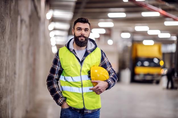 Operaio edile barbuto sveglio in maglia e con il casco di sicurezza nelle mani in piedi all'interno dell'edificio che sta ristrutturando.
