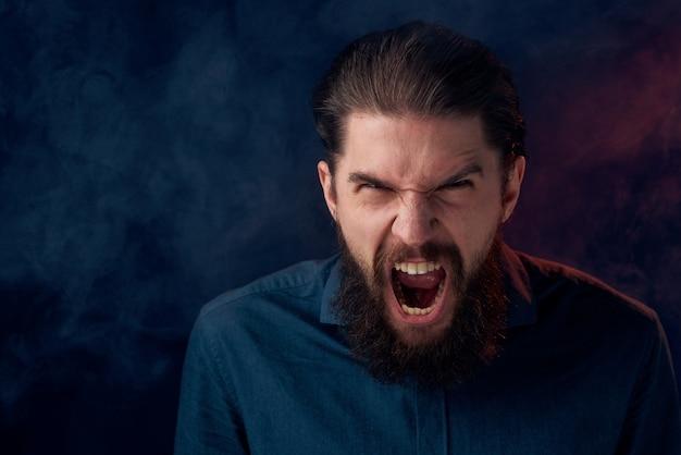 Uomo barbuto sveglio in fondo scuro del primo piano di stile elegante della camicia.