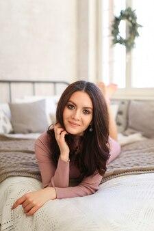 Una bella donna bruna carina in un abito da casa sta riposando su un letto in una camera da letto luminosa