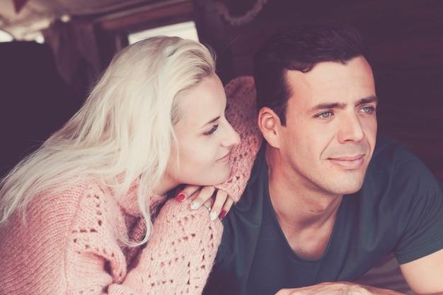 Carino bella coppia uomo e donna giovane caucasico soggiorno sdraiarsi insieme guardandosi con amore e relazione. filtro toni e colori vintage per un'immagine romantica