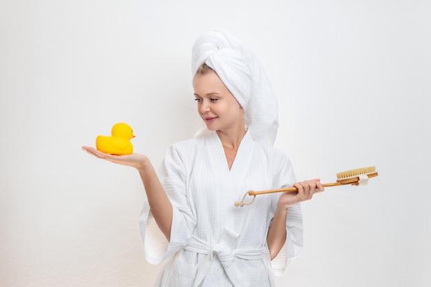 La bella ragazza sveglia in un accappatoio e un asciugamano sulla sua testa posa su un fondo bianco con un'anatra in una mano e una spazzola per il corpo nell'altra mano. concetto spa.