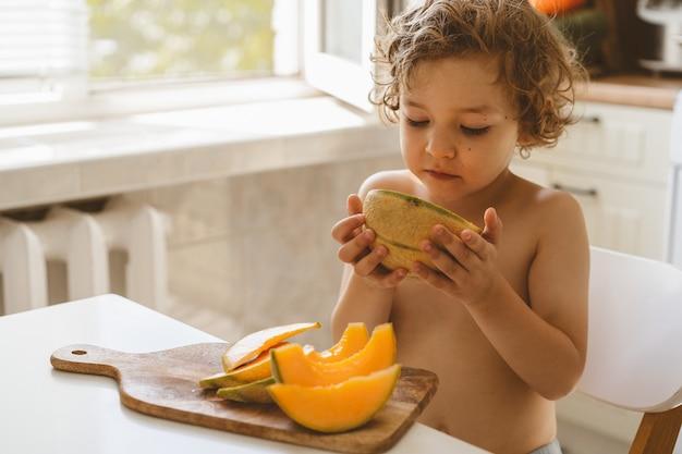 Bello ragazzino sveglio che mangia melone fresco.