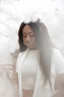Carino bella e tenera giovane donna di colore in un abito bianco su uno sfondo di fiori bianchi all'aperto. la bella ragazza africana alla moda in una maglietta bianca cammina vicino ai fiori. stile di vita di bellezza naturale