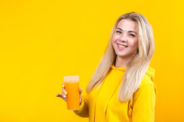 Bella giovane donna bionda sveglia in vestiti sportivi casuali gialli che tengono il vetro del succo d'arancia, ragazza sorridente isolata su fondo giallo