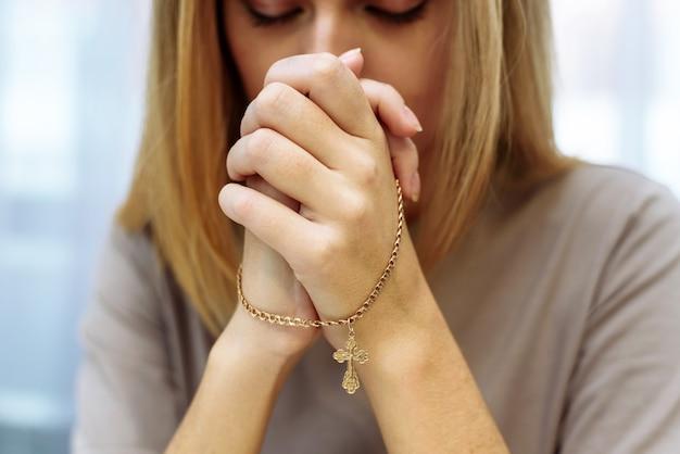 La bella giovane donna sveglia ha piegato le sue mani in preghiera.