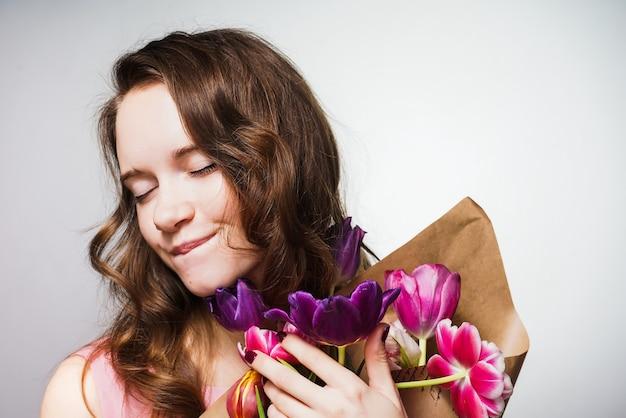 Carina bella giovane donna che tiene un grande mazzo di fiori, celebrando la giornata mondiale della donna, 8 marzo