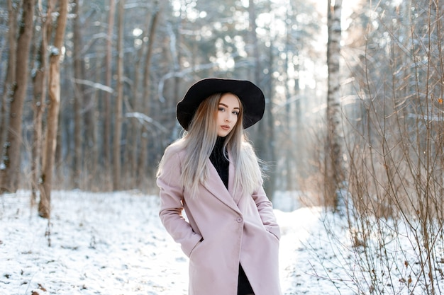 Bella giovane donna sveglia con capelli biondi in un cappello nero chic vintage in un cappotto elegante rosa in posa in un parco invernale. attraente ragazza alla moda.