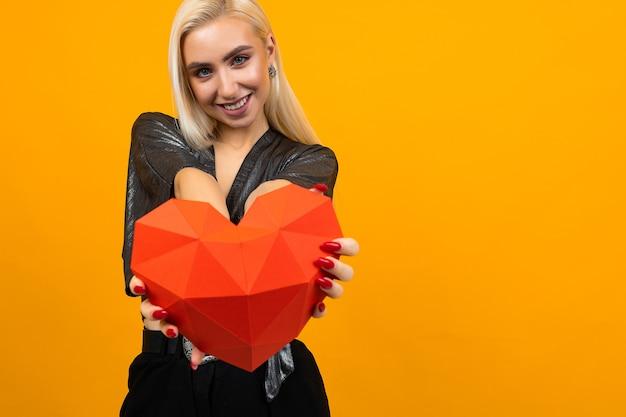 La ragazza bionda carina porge una figura di cuore 3d su un giallo Foto Premium