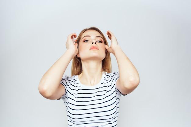 Ragazza bionda carina in studio di lifestyle di maglietta a strisce