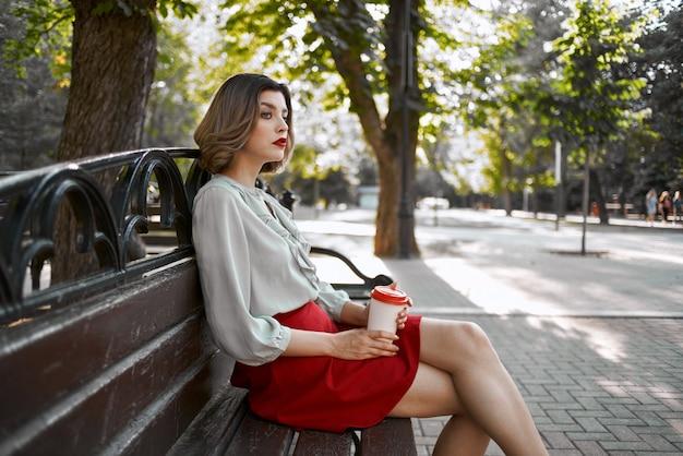 Bionda carina seduta su una panchina del parco che riposa una tazza di caffè