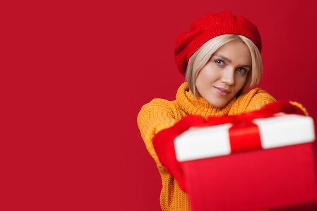 Carina donna bionda che indossa un cappello sta mostrando alla telecamera un presente in posa su un muro rosso