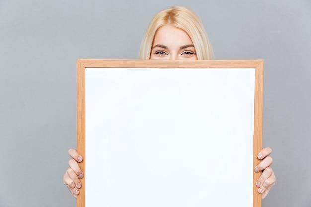 Carina giovane donna bionda che nasconde il viso dietro una lavagna bianca vuota su un muro grigio