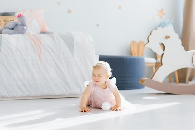Un simpatico bambino biondo dagli occhi azzurri di un anno in un vestito rosa sta tenendo strisciando a quattro zampe nella stanza dei bambini sul pavimento