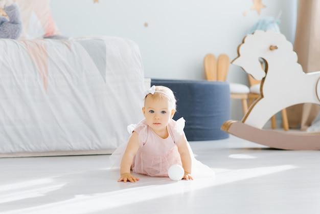 Il simpatico bambino di un anno con gli occhi azzurri e un vestito rosa continua a gattonare a quattro zampe nella stanza dei bambini sul pavimento