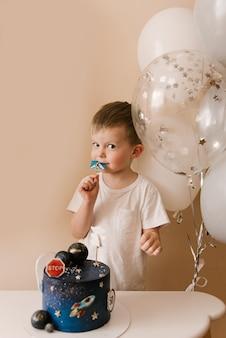 Il ragazzo carino di 3 anni festeggia il suo compleanno e mangia una deliziosa torta bellissima, foto di un bambino con palloncini