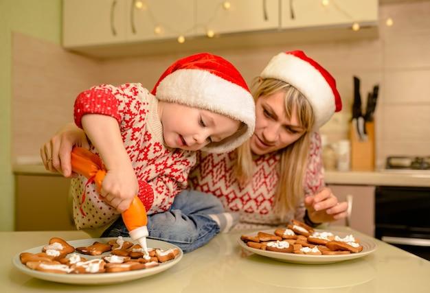 Ragazzo carino cuocere pan di zenzero festivi fatti in casa. il bambino divertente prepara il cibo di festa per babbo natale. santa kid rendendo il biscotto per la famiglia in cucina accogliente. aiutante di babbo natale.