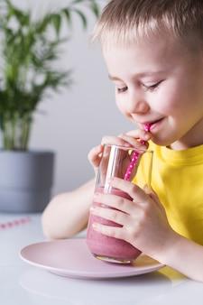 Un ragazzo carino beve un frullato di frutti di bosco da una cannuccia e sorride. il concetto di cibo sano.