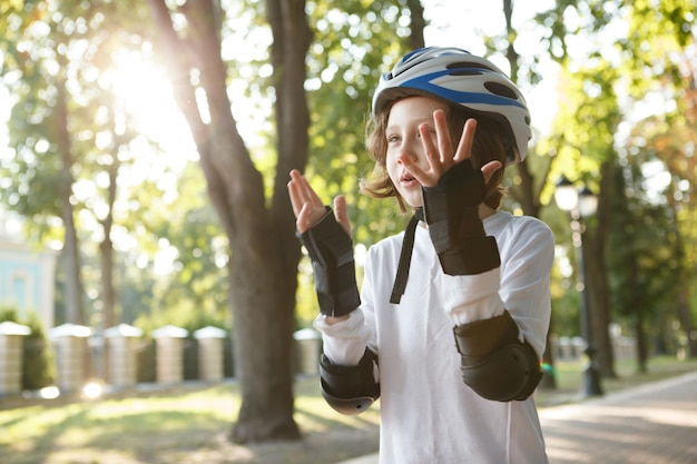 Ragazzo carino che si diverte a pattinare al parco, indossando indumenti protettivi per i rollerblade