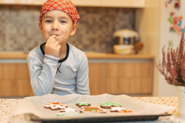 Ragazzo sveglio che gode del gusto dei biscotti di natale di appoggio freschi.