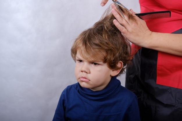 Aspetto europeo ragazzo carino durante il taglio di capelli con le forbici