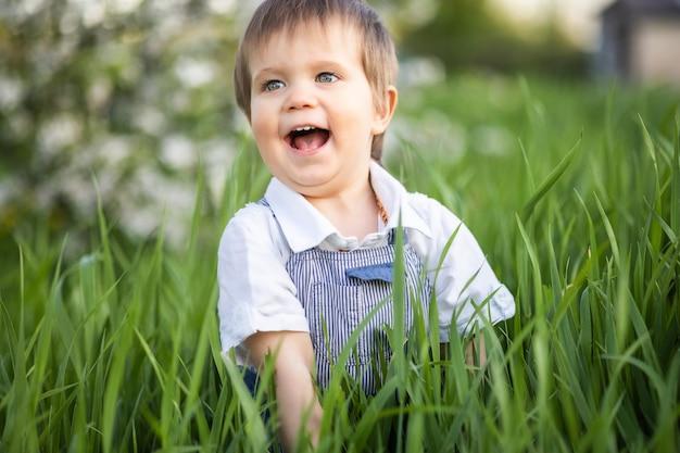 Ragazzo carino in abiti alla moda con gli occhi azzurri gioca e salta nell'erba alta in un grande giardino fiorito verde