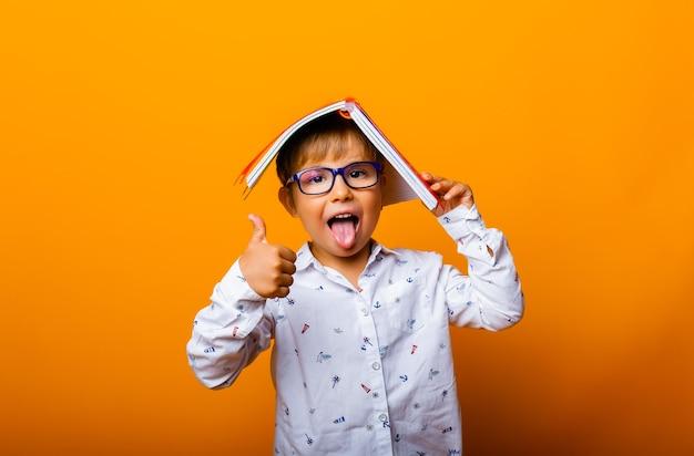 Ragazzo carino con gli occhiali con un libro in testa mostra la lingua su sfondo giallo