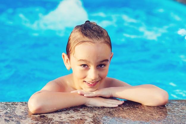 Ragazzo carino divertirsi in piscina. bambino felice che nuota nella piscina all'aperto. concetto di vacanza estiva. giochi d'acqua e divertimento acquatico per i bambini. ragazzo sorridente e riposante durante le vacanze.